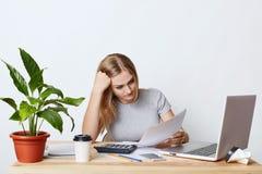 Überarbeitete Geschäftsfrau, die am Holztisch, umgeben mit den modernen Geräten, Dokumente aufmerksam lesend sitzt und versuchen  Stockbilder