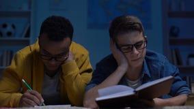 Überarbeitete jugendlich Studenten, die Mangel an Energie glauben, für Prüfung nachts spät sich vorzubereiten stock video footage