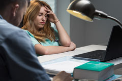 Überarbeitete Krankenschwester, die am Schreibtisch sitzt Lizenzfreie Stockbilder