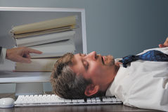 Überarbeiteter Angestellter, der bei der Arbeit schläft Stockfotografie