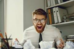 Überarbeiteter deprimierter schreiender Geschäftsmann beim Sitzen an seinem Schreibtisch Stockfoto