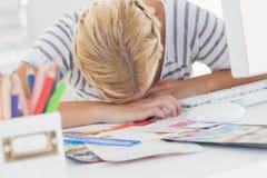 Überarbeiteter Designer, der auf ihrem Schreibtisch Nickerchen macht Stockbilder