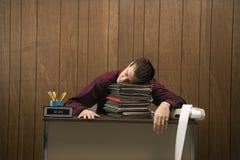 Überarbeiteter Retro- Geschäftsmann, der am Schreibtisch schläft. lizenzfreie stockfotos