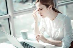 Überbelastete müde Frau, die Hauptschmerz bearbeitet und hat lizenzfreie stockbilder
