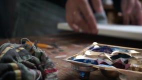 Überblick über die Werkzeuge eines Künstlers auf einer Tabelle, Farbenpalette, Lappen, Segeltuch wegnehmend stock footage