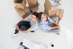 Überblick über ein glückliches Paar, das zurück zu Rückseite sitzt Lizenzfreie Stockfotos