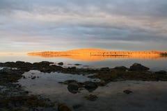 Überbrücken Sie hölzernes Dorf der Strandpiersonnenuntergangwolken See Lizenzfreie Stockbilder