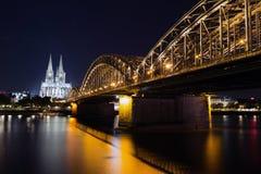 Überbrücken Sie und die Dom von Köln nachts lizenzfreie stockbilder