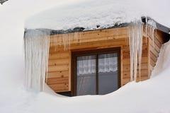 Überdachen Sie Fenster mit weißem Vorhang und mit Schnee und Eiszapfen um ihn lizenzfreies stockbild