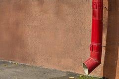 Überdachen Sie Gossenabflussrohr der roten Farbe auf Hausfassade Stockbild