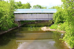 Überdachte Brücke, die im Fluss sich reflektiert Lizenzfreie Stockbilder