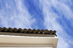 Überdachungsdach des Hauses mit einem gewellten Deckungsmaterial auf blauem Himmel des Hintergrundes bewölkt sich im Sommer Stockbilder