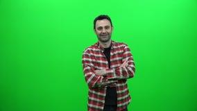 Überfahrtarme des jungen Mannes auf grünem Schirm stock footage