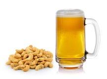 Überfallen Sie frisches Bier mit Kappe des Schaums und Acajounüsse häufen auf weißem Ba Lizenzfreie Stockbilder