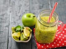 Überfallen Sie mit kürzlich gemachtem Kiwi Smoothie auf einem roten Lappen und ein Apfel und eine Zitrone auf einer rustikalen sc Stockbild