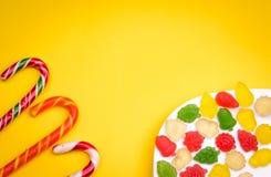 Überfluss an den Süßigkeiten und am Fruchtgelee auf einem gelben Hintergrund Stockbilder
