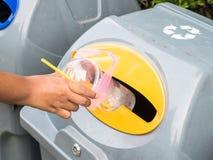 Übergeben Sie Abfall der Würfe weg in Abfall Stockbilder