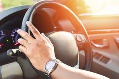 Übergeben Sie Abnutzung eine Uhr und fahren Sie ein Auto stockbild