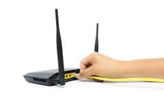 Übergeben Sie anschließendes gelbes Kabel zum Netzgerät, das auf weißem Hintergrund lokalisiert wird lizenzfreie stockfotografie