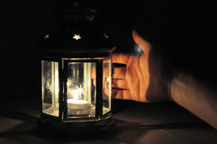 Übergeben Sie belichtetes wirt Licht von der Kerzenlaterne in der Dunkelheit Lizenzfreies Stockbild