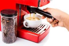 Übergeben Sie Brauenkaffee mit einer hellen rote Farbespressokaffeemaschine Stockfotos