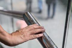 Übergeben Sie das Ablesen von Blindenschrift-Aufschriften für die Vorhänge auf Gemeinbedarfseinrichtungsgeländer Stockbild