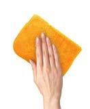 Übergeben Sie das Abwischen der Oberfläche mit dem orange Lappen, der auf Weiß lokalisiert wird Stockbild