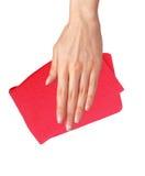 Übergeben Sie das Abwischen der Oberfläche mit dem roten Lappen, der auf Weiß lokalisiert wird Lizenzfreie Stockfotografie