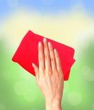 Übergeben Sie das Abwischen der Oberfläche mit rotem Lappen über hellem Fenster Stockbilder