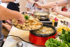 Übergeben Sie das Addieren des Bestandteiles in asiatische Dampfschifftopfmahlzeit Lizenzfreie Stockfotos