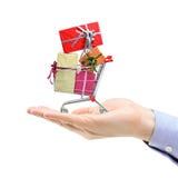 Übergeben Sie das Anhalten eines Einkaufswagens voll von den Geschenkkästen Lizenzfreie Stockfotos