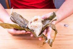 Übergeben Sie das Auspacken des chinesischen Reis Mehlkloßes oder zongzi auf Tabelle Lizenzfreie Stockfotografie