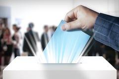 Übergeben Sie das Eingeben des Abstimmungspapiers in die Wahlurne Stockbilder