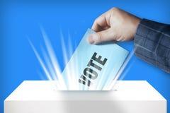 Übergeben Sie das Eingeben des Abstimmungspapiers in die Wahlurne auf blauen Hintergrund Lizenzfreies Stockfoto