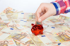 Übergeben Sie das Einsetzen der Euromünze in rotes Sparschwein auf Eurorechnungen Stockbild