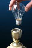 Übergeben Sie das Einsetzen einer Glühlampe in eine Lampe Lizenzfreies Stockbild