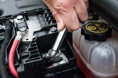 Übergeben Sie das Festziehen einer Klammer eines Automotors mit einem Schlüssel Stockfoto