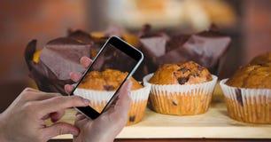 Übergeben Sie das Fotografieren von Muffins durch intelligentes Telefon an der Bäckerei stockbild