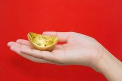 Übergeben Sie das Geben des Goldbarrens für Feier des Chinesischen Neujahrsfests auf Rot Stockfoto