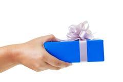 übergeben Sie das Geben eines Geschenks, das im blauen Kasten eingewickelt wird Lizenzfreie Stockfotos