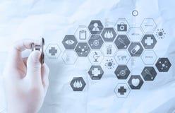 Übergeben Sie das Griffstethoskop, das medizinisches Konzept auf zerknittertem Papier zeigt Stockbild
