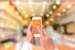 Übergeben Sie das Halten beweglich mit dem Bestellungslebensmittel, das mit Unschärferestaurant on-line ist Stockbild