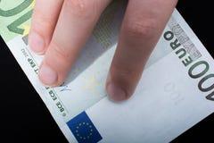 Übergeben Sie das Halten der Banknote des Euros 100 auf einem schwarzen Hintergrund Lizenzfreie Stockfotos