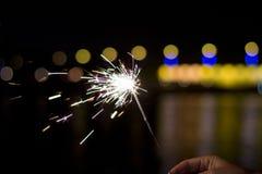 Übergeben Sie das Halten der brennenden Wunderkerze an neues Jahr ` s Vorabend Stockfoto