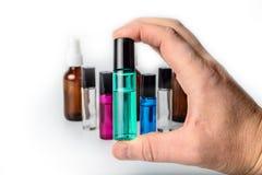 Übergeben Sie das Halten der Glasrollen-Flasche mit Flaschen im Hintergrund Stockbilder