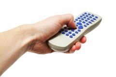 Hand, die graue Fernbedienung mit blauen Knöpfen hält Stockfotografie