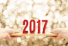 Übergeben Sie das Halten der hölzernen Platte mit einem roten Funkeln von 2017 guten Rutsch ins Neue Jahr numerisch Stockfotos