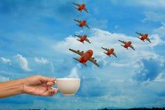 Übergeben Sie das Halten der Kaffeetasse mit Flugzeugmodellen auf Himmelhintergrund, stockfotografie