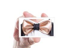 Übergeben Sie das Halten der Karte mit goldenem ledernem bowtie Bild Lizenzfreies Stockbild