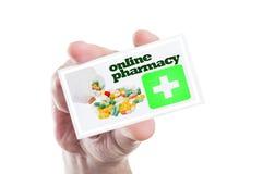 Übergeben Sie das Halten der Karte mit on-line-Apotheke, grünem Kreuz und Pillen Lizenzfreies Stockfoto